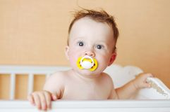 Funny baby with dummy in white bed. Funny baby age of 10 months with dummy in white bed Royalty Free Stock Image