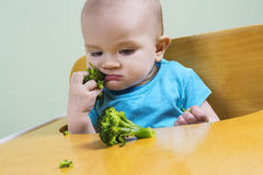 Funny baby eating broccoli Royalty Free Stock Images