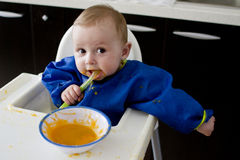 Funny baby eating diversification. Funny baby eating diversified food (pureed fruits), wearing protective bib stock images