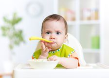 Funny baby eating food on kitchen Stock Image