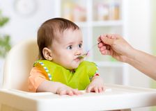 Funny baby eating food on kitchen. Funny baby girl eating food on kitchen stock photo
