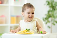 Funny baby eating healthy food in daycare. Funny baby boy eating healthy food in nursery Stock Photography