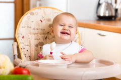 Funny baby eating in high-chair on kitchen royalty free stock photography