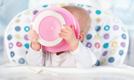 Funny baby is eating from pink plate Royalty Free Stock Images
