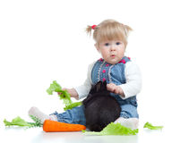 Funny baby feeding rabbit a carrot and lettuce Stock Photography