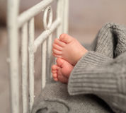 Funny baby feet out of gray pants on cot. Funny bare baby feet out of gray pants on old cot with headboard, closeup Stock Photography