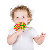 Funny baby girl with a big colorful candy Stock Photography