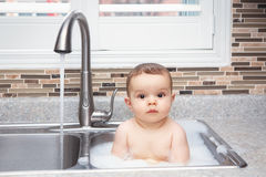 Funny baby girl boy with dark black eyes sitting in big kitchen sink with water and foam. Portrait of cute Caucasian funny baby girl boy with dark black eyes stock photography