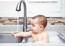 Funny baby girl boy with dark black eyes sitting in big kitchen sink with water and foam. Portrait of cute Caucasian funny baby girl boy with dark black eyes Royalty Free Stock Images