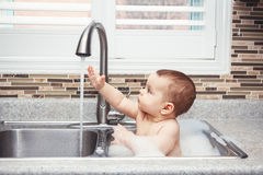 Funny baby girl boy with dark black eyes sitting in big kitchen sink with water and foam. Portrait of cute Caucasian funny baby girl boy with dark black eyes stock images