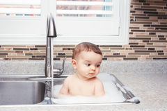 Funny baby girl boy with dark black eyes sitting in big kitchen sink with water and foam. Portrait of cute Caucasian funny baby girl boy with dark black eyes Stock Image