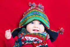 Funny baby girl in colorful knitted hat and scarf Stock Photos