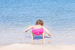 Funny baby girl drinking water on beach Stock Photos