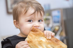 Funny baby girl eating bread Stock Image
