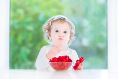 Funny baby girl eating raspberry at white table Stock Photography