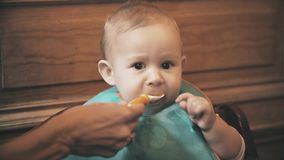 Funny baby girl eats unappetizing meal and frowns, close-up royalty free stock photo