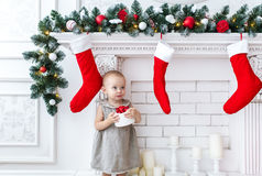 Funny baby girl with gift boxes against the background of a white brick wall. New year Stock Photo