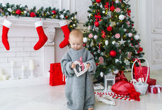 Funny baby girl with gift boxes and Christmas tree on background. Royalty Free Stock Images