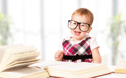 Funny baby girl in glasses reading a book Royalty Free Stock Photos