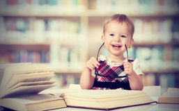 Funny baby girl in glasses reading a book. Happy funny baby girl in glasses reading a book in a library stock images