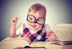 Funny baby girl in glasses reading a book. Happy funny baby girl in glasses reading a book in a library stock photography
