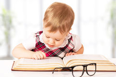 Funny baby girl in glasses reading a book. Happy funny baby girl in glasses reading a book in a library royalty free stock photos