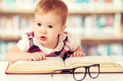 Funny baby girl in glasses reading a book in library royalty free stock photos