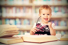Funny baby girl in glasses reading a book in a library Stock Images