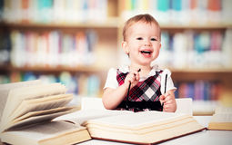 Funny baby girl in glasses reading a book in a library Stock Photo