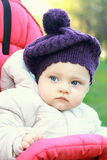 Funny baby girl in hat outdoor sit Royalty Free Stock Photography