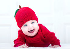 Funny baby girl in knitted apple hat playing on her tummy Royalty Free Stock Photo