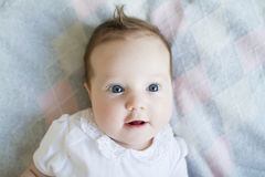 Funny baby girl on a knitted grey blanket. Funny baby girl with blue eyes on a knitted grey blanket Royalty Free Stock Photography