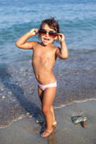Funny baby girl with large sunglasses. Funny baby girl with large sunglasses at the seaside Royalty Free Stock Photography
