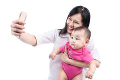 Funny baby girl looking at the camera and smiling, make selfie on mobile phone Stock Image