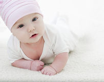 Funny baby girl lying on white Royalty Free Stock Photography