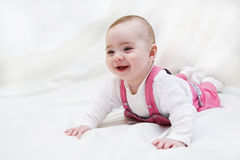 Funny baby girl lying on white. And smile stock photos