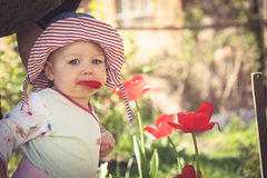 Funny baby girl in panama hat walking in park among blossoming flowers in sunny summer day with copy space. Royalty Free Stock Photo