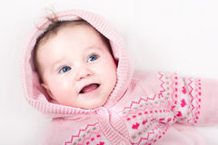 Funny baby girl in pink jacket with hearts pattern Stock Images