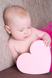 Funny baby girl in pink skirt with heart sitting Royalty Free Stock Images