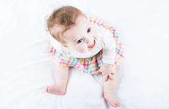 Funny baby girl in a plaid skirt sitting on a whit Stock Images