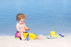 Funny baby girl playing on a beautiful beach Royalty Free Stock Photos