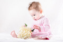 Funny baby girl playing with a big flower Royalty Free Stock Photo