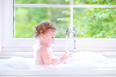 Funny baby girl playing in big kitchen sink with f. Funny little baby girl with wet curly hair taking a bath in a kitchen sink with lots of foam playing with royalty free stock photos