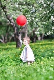 Funny baby girl playing with a big red balloon Royalty Free Stock Photography