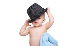 Funny baby girl playing with black hat Royalty Free Stock Images
