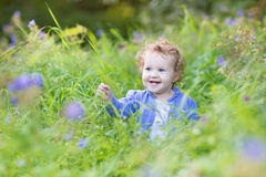 Funny baby girl playing in a blooming garden Royalty Free Stock Image