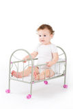 Funny baby girl playing in a doll bed. On white background Royalty Free Stock Image