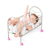 Funny baby girl playing in a doll bed Stock Image