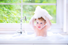 Funny baby girl playing with foam in big kitchen sink. Funny little baby girl with wet curly hair taking a bath in a kitchen sink with lots of foam playing with royalty free stock photos