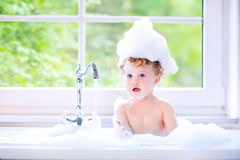 Funny baby girl playing with foam in big kitchen sink Stock Images